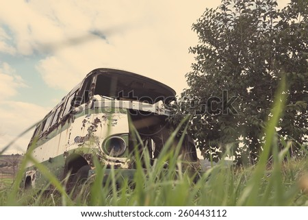 Abandoned old bus in a green field. Edited image with vintage washed colors - stock photo