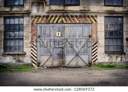 Abandoned old factory with closed door and windows - stock photo