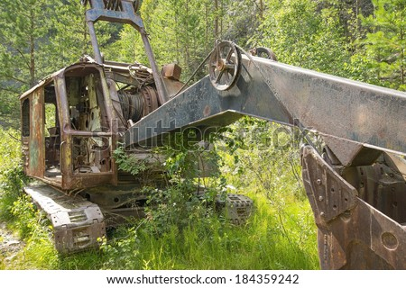 Abandoned old rusty excavator in summer fresh green forest and grass