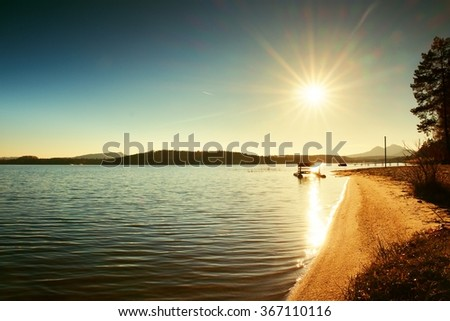 Abandoned old rusty paddle boat stuck on sand of beach. Wavy water level, island on horizon. Autumn sunny weather at coastline  - stock photo