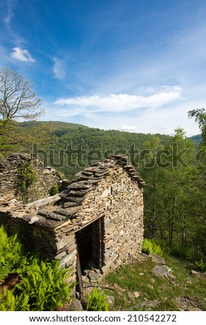 Abandoned old stones house with blue sky and forest in the background in the north of Italy, Scareno, close to verbania. - stock photo