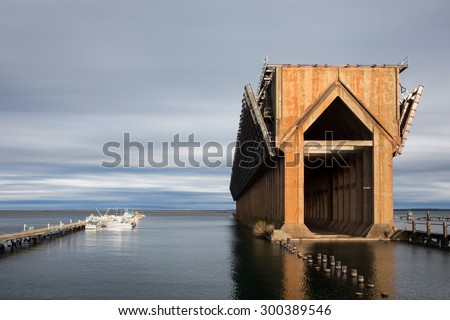 Abandoned ore dock once used to transfer coal and other materials between railroad cars and Lake Superior ore boats. Geometric structure captured near sunset.  Copy space and smaller boats for scale. - stock photo