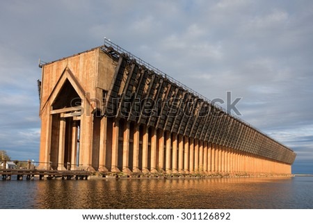 Abandoned ore dock once used to transfer coal and other materials between railroad cars and Lake Superior ore boats. Interesting geometric structure captured near sunset. Warm light and dramatic sky. - stock photo