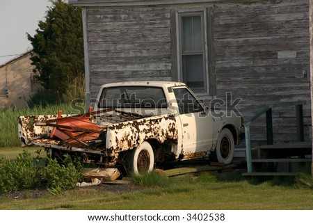 Abandoned pickup truck in front of derelict house