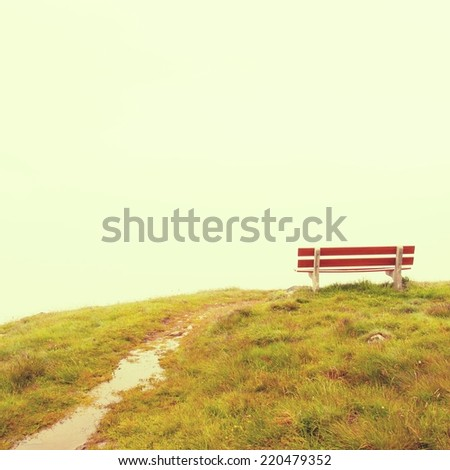 Abandoned red bench on hill view point. September misty evening on the hill in Switzerland Alps. Red wooden bench on meadow, cold rainy and misty weather.  - stock photo