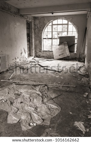 Abandoned room in disarray with broken glass and sheets on floor