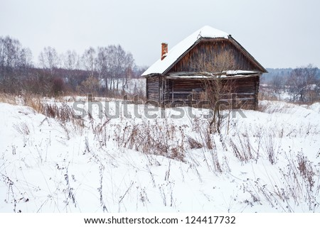 abandoned rustic house in snow-covered village in winter day - stock photo