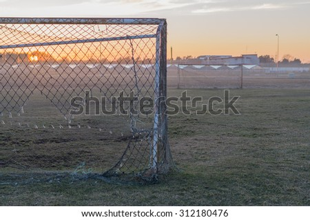 Abandoned soccer field and old rusty goals on sunset, nostalgia concept - stock photo