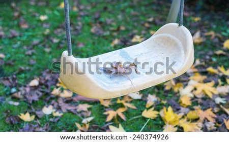 Abandoned swing on a park in autumn. - stock photo