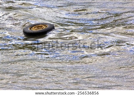 Abandoned tire flows into a river with copy space - stock photo