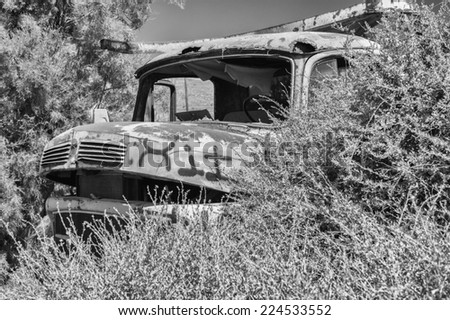 Abandoned truck in the middle of a grass field. - stock photo