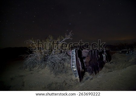 Abandoned vintage auto in the desert, under the stars, Joshua Tree National Park - stock photo