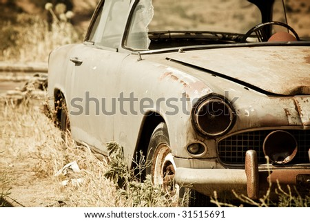 Abandoned vintage car in the middle of nowhere - stock photo