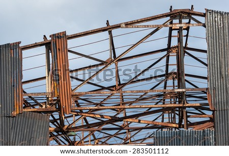 Abandoned warehouse with exposed rusting girders. - stock photo