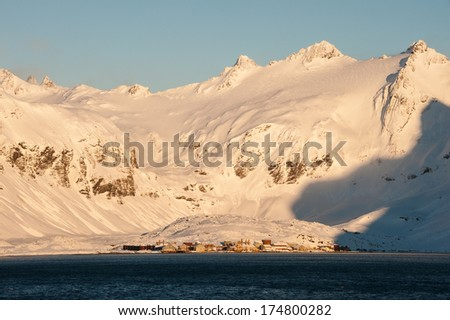 Abandoned whaling station in antarctica with snowy mountain in background. - stock photo