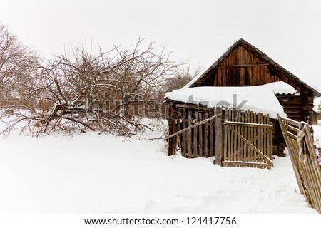 abandoned wooden shed in snow-covered village in winter day - stock photo