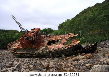 Abandoned wrecked fishing trawler beached on the shore - stock photo