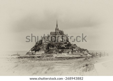 Abbey Mont Saint-Michel (7th century) at rocky tidal island in Normandy - one of most visited tourist sites in France. Mont-Saint-Michel in UNESCO list of World Heritage Sites. Antique vintage. - stock photo