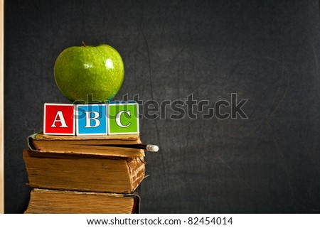 ABC and green apple on old textbook against blackboard in class. School concept - stock photo