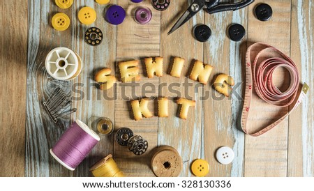 ABC Cookie in the form of word SEWING KIT and sewing tools on vintage wooden background. Copy-Space - stock photo