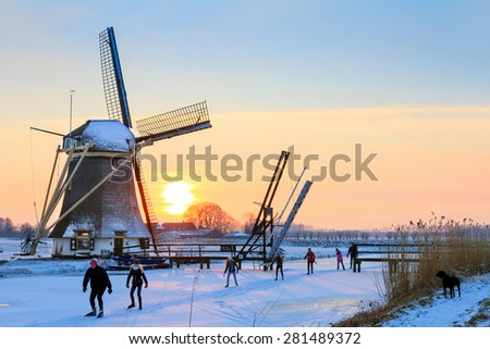 ABCOUDE, THE NETHERLANDS - FEBRUARY 4, 2012: Beautiful typical dutch scene with a family ice skating home at sunset past a old windmill near Abcoude in the Netherlands, on February 4, 2012 - stock photo