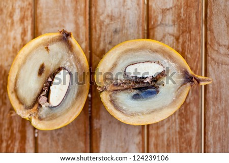 Abiu Fruit cut in half on wooden table - stock photo