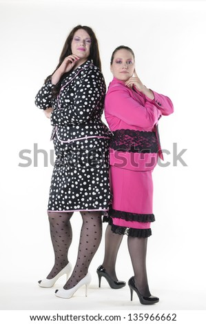 About two faithfully models wear flashy costumes and have fun together, they stand back to back and are friends, isolated against white background.