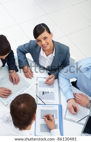 Above angle of beautiful secretary looking at camera in working environment - stock photo