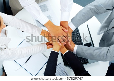 Above angle of business partners making pile of hands over workplace - stock photo