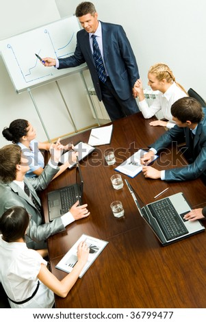 Above angle of business people listening to confident man during seminar - stock photo