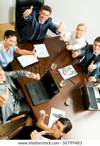 Above angle of business people showing thumbs up and looking at camera