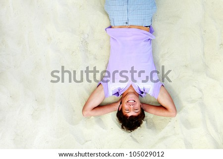 Above angle of handsome teenager lying on sand and laughing - stock photo