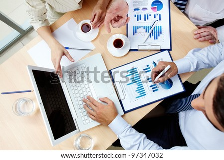 Above angle of human hands with business documents and laptop at meeting - stock photo