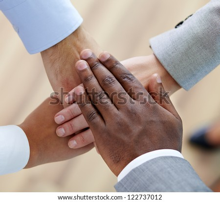 Above angle of pile of hands of business partners - stock photo