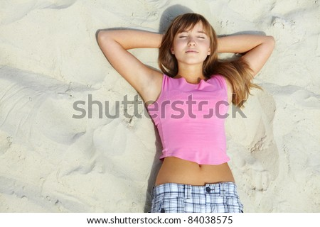 Above angle of pretty teenager lying on sandy beach - stock photo