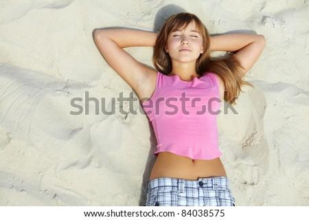 Above angle of pretty teenager lying on sandy beach - stock photo