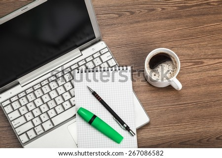Above. Blank notepad over laptop and coffee cup on office wooden table - stock photo