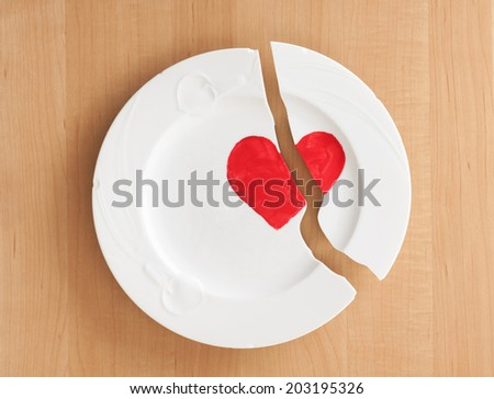 Above Closeup View of a broken ceramic china White Plate with a red Heart Painted on it.  Wood board background.   Concept for relationship, friendship or marriage troubles. - stock photo
