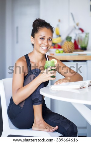 Above shot of a woman with a bowl of berries, a bottle of almond milk and two bananas wearing a sportive outfit. non-diary - stock photo