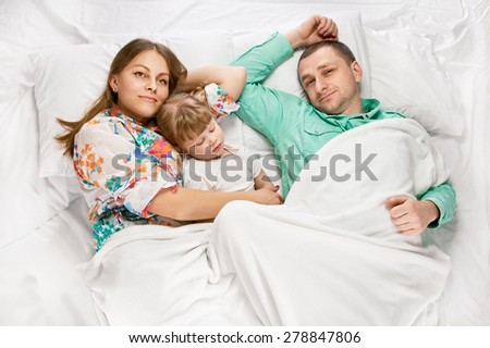 Above view of a family lying on the bed, parents playing with their little daughter - stock photo