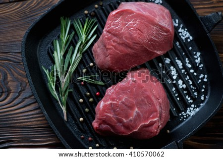 Above view of a grill pan with raw beef fillet mignon steaks - stock photo