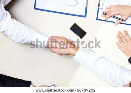 Above view of business handshake after signing contract - stock photo