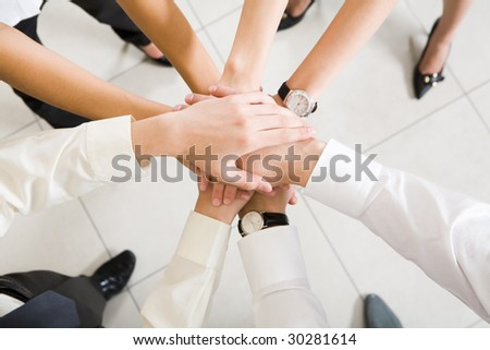 Above view of business partners hands on top of each other symbolizing teamwork and respect - stock photo