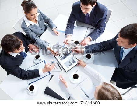 Above view of business team discussing papers at meeting - stock photo