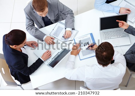 Above view of business team sitting around table and working - stock photo