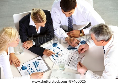 Above view of businesspeople looking at schemes and diagrams - stock photo