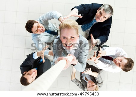 Above view of businesswoman ascending up the rope with supporting crew beneath - stock photo