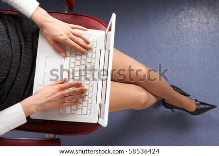 Above view of businesswoman typing on laptop in office - stock photo