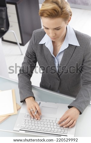 Above view of elegant businesswoman sitting at desk, working on laptop computer, typing on keyboard. - stock photo