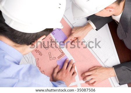 Above view of engineers looking at blueprints with sketches of projects - stock photo